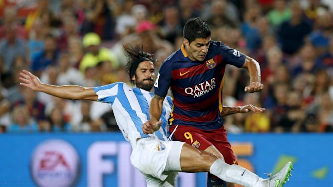 Barcelona's Suarez tries to score as Malaga's Angeleri challenges him during their Spanish first division soccer match at Camp Nou stadium in Barcelona