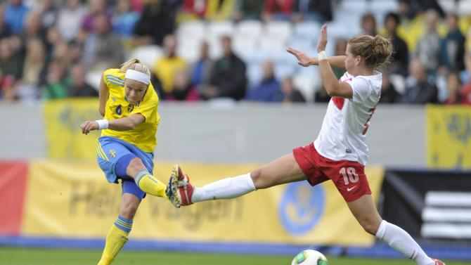 Poland's Evelyn Nicinski, right, tries to block a shot from Sweden's Sara Thunebro, left, during the ladies' football World Championships qualification match at Swedbank Stadium in Malmo, Sweden, Saturday Sept. 21, 2013. (AP Photo / Scanpix Sweden,Bjorn Lindgren)
