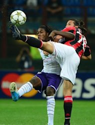 Anderlecht's forward Dieumerci Mbokani (L) fights for the ball with AC Milan's Mario Yepes during their Champions League football match at the San Siro Stadium in Milan