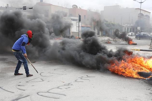 A Libyan protester stands next burning tyres as residents block a street in the capital Tripoli on March 2, 2014