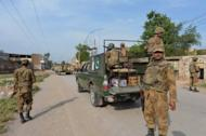 Pakistani army soldiers patrol a street on the outskirts of Peshawar on May 10, 2013. A bomb attack has killed 14 people and wounded more than 25 others at a Shiite Muslim mosque and religious seminary on the outskirts of the city officials say.