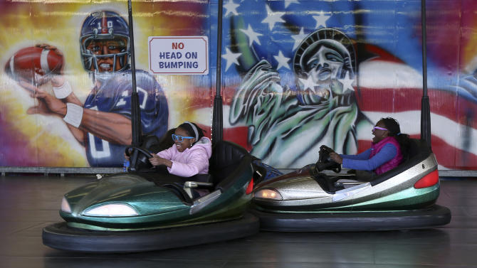 In this Saturday, March 30 2013 photo, children drive the bumper cars at Deno's Famous Wonder Wheel Amusement Park in New York's Coney Island.  Despite making the traditional Palm Sunday opening, many of the seasonal businesses at Coney Island are still reeling from the aftermath of Superstorm Sandy. (AP Photo/Mary Altaffer)