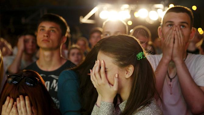 People supporting Dnipro Dnipropetrovsk of Ukraine react while watching the Europa League soccer final match against Sevilla of Spain in the capital Kiev