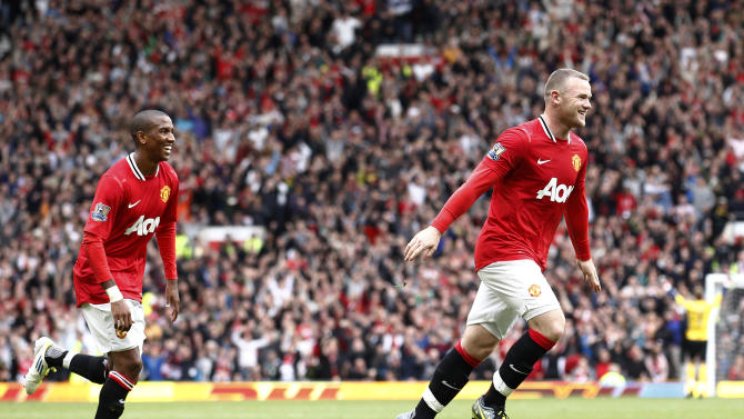 Manchester United's Wayne Rooney, right, celebrates with team mate Ashley Young after he scored a goal against Arsenal during their English Premier League soccer match at Old Trafford, Manchester, England, Sunday Aug. 28, 2011. (AP Photo/Jon Super)