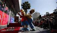 "The characters of Homer (R) and Bart Simpson pose by the star of Matt Groening, creator of ""The Simpsons,"" before it was unveiled on the Walk of Fame in Hollywood, California February 14, 2012. REUTERS/Mario Anzuoni"