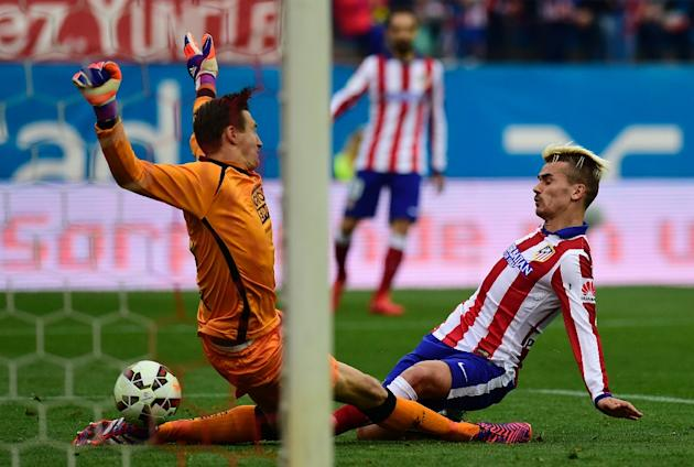 Atletico Madrid's French forward Antoine Griezmann (R) scores his second goal after beating Elche's Polish goalkeeper Przemyslav Tyton during the Spanish league football match in Madrid on Apr