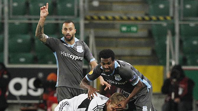 Christos Karipidis,right, and Fotis Papoulis ,left, of  Apollon Limassol FC challenges for the ball with Jakub Rzezniczak ,center, of Legia Warsaw, during their Europa League group J soccer match at in Warsaw, Poland, Thursday, Oct. 3, 2013