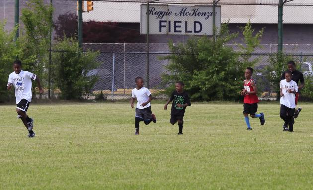 In this photo taken June 17, 2015, kids run a lap in McKenzie field during a football camp in Highland Park, Mich. Former NFL star and Highland Park native Reggie McKenzie had to go into his own pocke