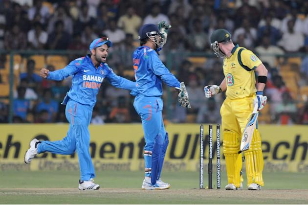 Indian players Virat Kohli and M S Dhoni celebrate a wicket during the 7th ODI between India and Australia played at Chinnaswamy Stadium in Bangalore on Nov.2, 2013. (Photo: IANS)