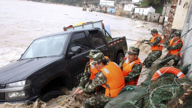 Paramilitary policemen pull up a vehicle overturned by a storm surge near the coastline, under the influence of Typhoon Fitow in Yuhuan