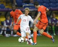Danish forward Tobias Mikkelsen (C) vies with Dutch midfielder and captain Mark van Bommel (R) and Dutch defender Jetro Willems during their Euro 2012 football group match