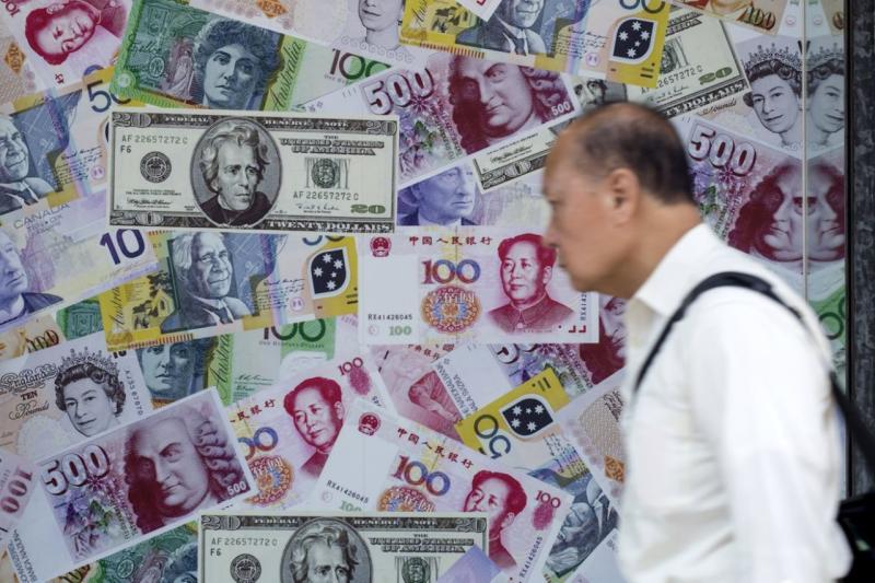 Un hombre camina delante de un anuncio que promociona servicios de cambio de renminbis (RMB) o yuanes chinos, dólares estadounidenses y euros en una casa de cambio de divisas extranjeras en Hong Kong, China (REUTERS / Tyrone Siu).
