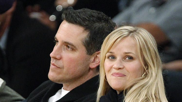 FILE - In this Friday, March 8, 2013 file photo, actress Reese Witherspoon and her husband, Jim Toth, watch the Toronto Raptors take on the Los Angeles Lakers in an NBA basketball game in Los Angeles. Police in Georgia say that Witherspoon has been arrested on a disorderly conduct charge after a traffic stop involving her husband in Atlanta. A Georgia State Police incident report says that Witherspoon was arrested early Friday, April 19, 2013, and charged with disorderly conduct. The report says a state trooper observed that a car driven by Toth was failing to stay in its lane. The officer writes that Witherspoon disobeyed multiple orders to stay in the car while he performed a field sobriety test on Toth. After she refused to return to the car, she was handcuffed and arrested. (AP Photo/Reed Saxon, File)