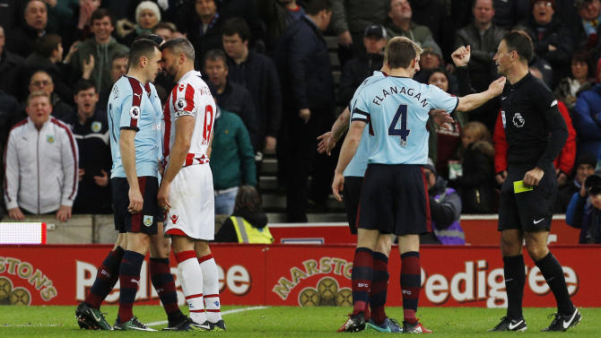Burnley's Dean Marney clashes with Stoke City's Jonathan Walters as referee Mark Clattenburg looks on