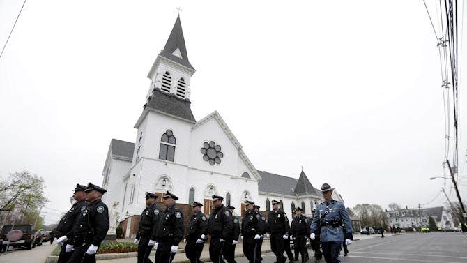 Massachusetts Institute of Technology police officers march as they depart St. Patrick's Church in Stoneham, Mass., following a funeral Mass for MIT police officer Sean Collier, Tuesday, April 23, 2013. Collier was fatally shot on the MIT campus Thursday, April 18, 2013. Authorities allege that the Boston Marathon bombing suspects were responsible. Law enforcement official at right is unidentified. (AP Photo/Steven Senne)