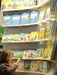 A young visitor reads a book at a booth of the Leipzig Book Fair last month. Mum-of-five Maya Ammouri from Berlin said she will not a new benefit to keep her children at home, preferring to send her children to nursery early for the stimulus they cannot always get at home with a busy parent