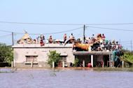 Residents on the roof of a house surrounded by floodwaters in Chokwe district, southern Mozambique, on January 25, 2013. Intense flooding in Mozambique has displaced at least 150,000 people, the United Nations said Monday, with the figure expected to rise further as fresh rains spread flooding northward