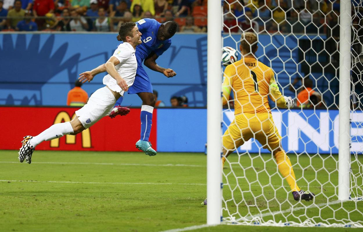 Italy's Balotelli heads the ball to score past England's Cahill and Hart during their 2014 World Cup Group D soccer match at the Amazonia...