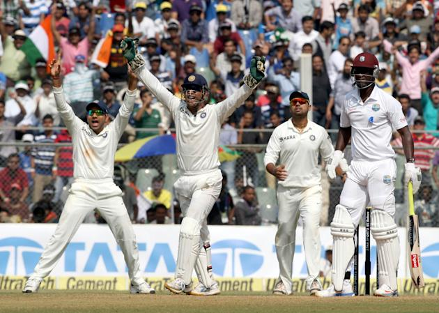 Indian cricketers celebrate fall of a wicket during the 3rd day of the 2nd Test Match between India and West Indies at Wankhede Stadium in Mumbai on Nov.16, 2013. (Photo: IANS)