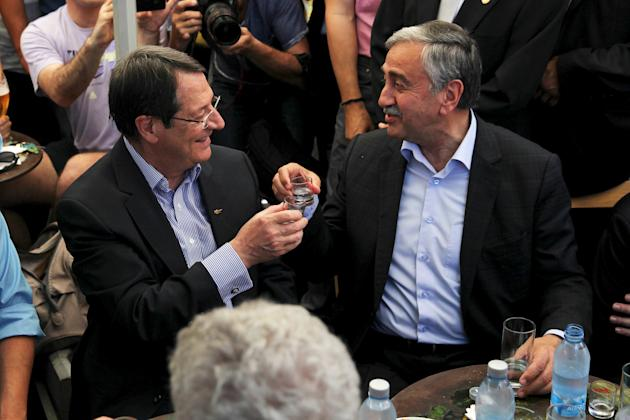 Turkish Cypriot leader Mustafa Akinci and Greek Cypriot leader, Cypriot President Nicos Anastasiades clink glasses in old Nicosia