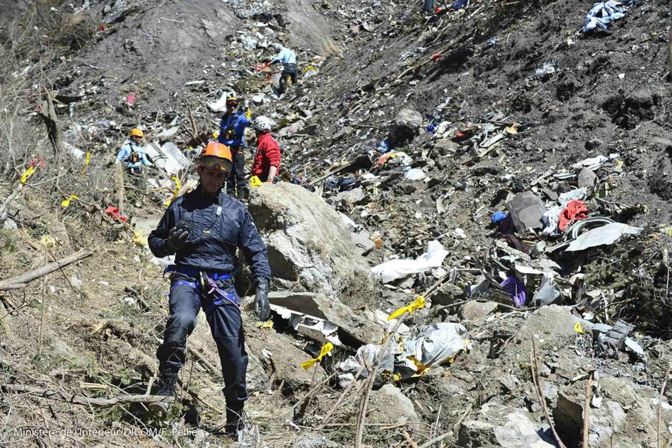 French gendarmes and investigators, seen in this picture released by the French Interior Ministry, make their way through debris from wreckage on the mountainside at the crash site of an Airbus A320,