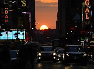 The sun sets as seen from 42nd street in New York City on July 11, 2012, as Manhattanhenge