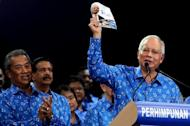 Malaysian Prime Minister Najib Razak (right) holds a copy of his coalition's election manifesto during a rally in a suburb of Kuala Lumpur on April 6, 2013. Razak unveiled a manifesto on Saturday pledging bigger cash handouts, millions of new jobs and lower taxes and crime, as he seeks his first mandate in looming national polls