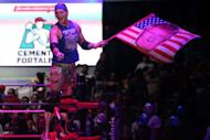U.S. wrestler Sam Adonis, 27, role-playing as a fan of U.S. President Donald Trump, waves a flag with Trump's face during a wrestling fight at the Coliseo Arena in Mexico City, Mexico, February 12, 2017. Picture taken, February 12, 2017. REUTERS/Edgard Garrido
