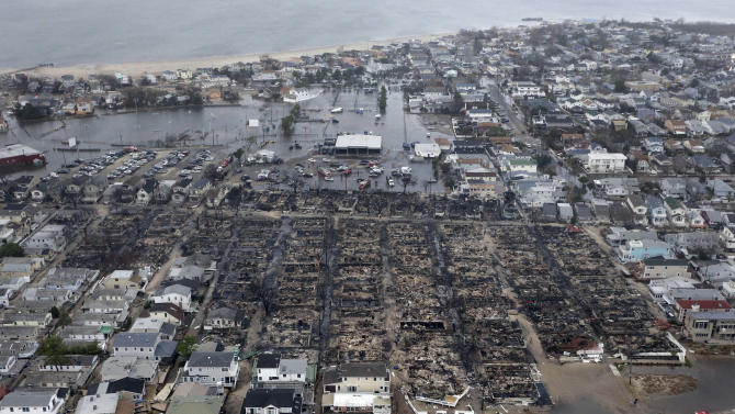 FILE - This Oct. 30, 2012 file aerial photo shows burned-out homes in the Breezy Point section of the Queens borough New York after a fire. The tiny beachfront neighborhood told to evacuate before Sandy hit New York burned down as it was inundated by floodwaters, transforming a quaint corner of the Rockaways into a smoke-filled debris field. Superstorm Sandy wreaked havoc on parts of the U.S. East Coast a month ago today after tearing through the Caribbean. In the weeks since, the storm's scope has come into sharper focus. (AP Photo/Mike Groll, File)