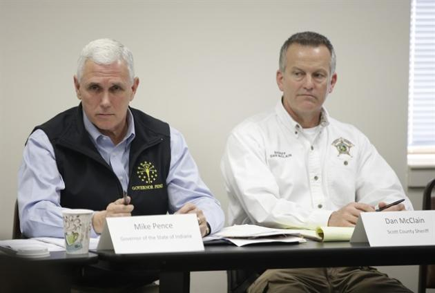 Indiana Gov. Mike Pence makes a comment as Scott County Sheriff Don McClain listens during a meeting that Pence held with local officials in Scott County to discuss an HIV outbreak in the area, Wednes