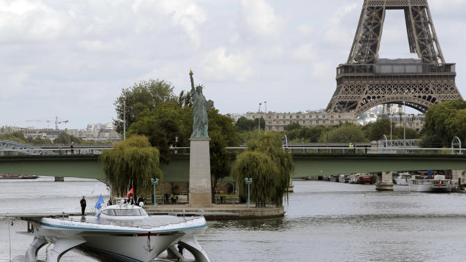 The Turanor PlanetSolar, the world's largest solar boat, travels on the Seine river as the Eiffel Tower is seen in background, in Paris, Tuesday, Sept. 10, 2013. The PlanetSolar with its 537 square meters of photovoltaic panel powering 6 blocks of lithium-ion batteries, accomplished the first around the world trip powered only by solar energy in May 2012. (AP Photo/Christophe Ena)
