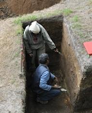 Scientists crouch at an excavation where they are studying sediment layers in the Russian Far East to look for signs of past seismic hazards.