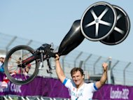 Italy's Alessandro Zanardi holds his bike aloft as he celebrates after winning the gold medal in the men's individual H4 time trial cycling final during the London 2012 Paralympic Games at Brands Hatch circuit, in Kent. Zanardi won again at a motor racing circuit by taking Paralympic gold in the men's individual H4 (hand-cycle) time-trial