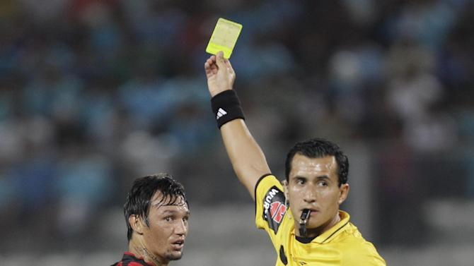 Chile's referee Enrique Osses, right, shows a yellow card to Joao Paulo of Brazil's Atletico Paranaense during a Copa Libertadores soccer match against Peru's Sporting Cristal in Lima, Peru, Wednesday, Jan. 29, 2014