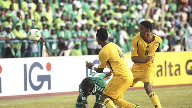 Nigeria's Victor Moses, left, is challenged by Ethiopia's Abebaw Butako, left, and Asrat Mekersa, right, during their 2014 World Cup qualifying soccer match at U. J. Esuene Stadium, in Calabar, Nigeria, Saturday, Nov. 16, 2013.  Nigeria defeated Ethiopia 2-0 to qualify for the World Cup in Brazil