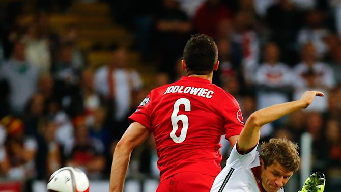 Poland's Jodlowiec challenges Germany's Mueller during their Euro 2016 qualification match in Frankfurt