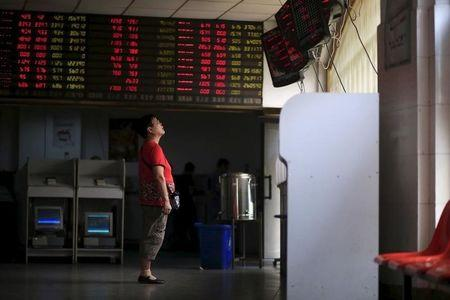 An investor looks at electronic boards showing stock information at a brokerage house in Shanghai, China, September 1, 2015. REUTERS/Aly Song