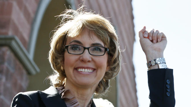 "FILE - In this Wednesday, March 6, 2013 file photo, former U.S. Rep. Gabrielle Giffords smiles as she raises a fist pump to the crowd as she, husband Mark Kelly, and a number of other Tucson mass shooting victims returned to the site of the shooting in Tucson, Ariz., that left her critically wounded to urge key senators to support expanded background checks for gun purchases. Giffords has been named this year's recipient of the John F. Kennedy Profile in Courage award. The JFK Library and Museum announced Friday that the Arizona Democrat is being honored for the ""political, personal, and physical courage she has demonstrated in her fearless public advocacy for policy reforms aimed at reducing gun violence."" (AP Photo/Ross D. Franklin, File)"