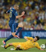 French forward Karim Benzema (L) jumps over Ukrainian defender Taras Mikhalik during the Euro 2012 championships football match at the Donbass Arena in Donetsk. France won 2-0