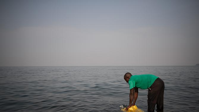 A man fills a jerrycan with water from Lake Kivu on the Himbi beach in Goma, in the east of the Democratic Republic of Congo on August 11, 2013