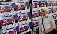 A local resident walks past posters of Russian President Vladimir Putin, reading 'Welcome, President', in Belgrade, Serbia, on October 15, 2014, on the eve of his visit
