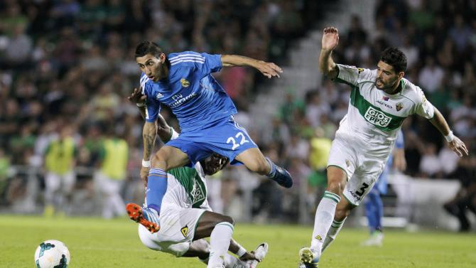Real Madrid's Di Maria is tackled by Elche's Sanchez as Botia watches during Spanish first division soccer match in Elche