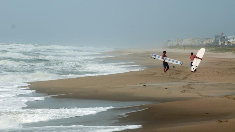 Surfers check out the waves at Kure Beach, N.C. as Tropical Storm Andrea hugs the North Carolina coast on Friday, June 7, 2013.  The storm was racing through South Carolina early Friday and was expected to move into eastern North Carolina by midday.  (AP Photo/The Star-News, Paul Stephen )