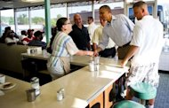 US President Barack Obama shakes hands with a waitress as he arrives at Ann's Place in Akron, Ohio, during an unannounced visit while on a bus tour of Ohio and Pennslyvania