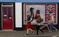 Youths walk past a shop, which has been covered with artwork to make it look more appealing, in the village of Bushmills on the Causeway Coast August 20, 2013. REUTERS/Cathal McNaughton