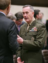 International Security Assistance Force and United States Forces-Afghanistan (ISAF) Commander General Joseph Dunford talks with other delegates before a bilateral meeting at NATO headquarters on February 22, 2013 in Brussels. NATO may station up to 12,000 troops in Afghanistan to train and assist Kabul's forces after its combat mission against the Taliban ends there in 2014, US officials said