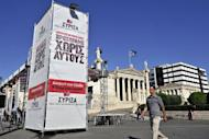 People walk by the main election campaign kiosk of the Communists and leftist Syriza party ahead of the May 6 parliamentary elections in Athens. Elections on Sunday will define Greece's future for decades to come, outgoing Prime Minister Lucas Papademos said Wednesday, urging his successors to stick by unpopular and vital austerity measures