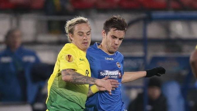Anzhi's Andrey Eschenko, left, and Tromso's Remi Johansen struggle for the ball during the Europa League group K soccer match between Anzhi Makhachkala and Tromso IL at Saturn stadium in Ramenskoye, outside Moscow, in Russia, on Thursday, Oct. 24, 2013