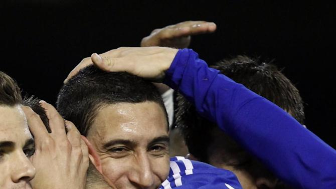 Real Madrid's  Angel Di Maria from Argentina, center, is congratulated by teammate after scoring a goal against Valencia during their La Liga soccer match at the Mestalla stadium in Valencia, Spain, Sunday, Dec. 22, 2013