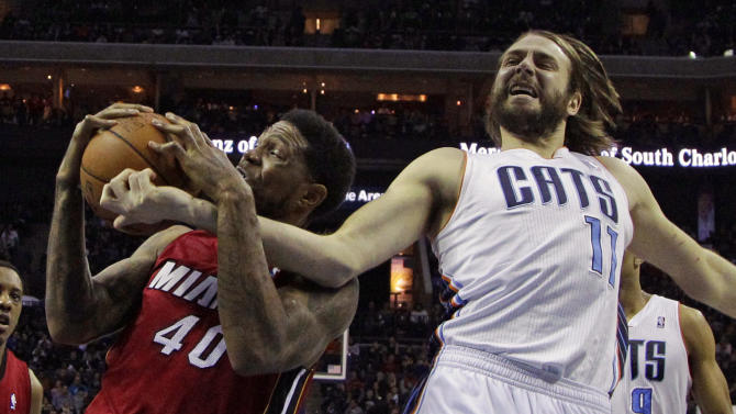 Charlotte Bobcats' Josh McRoberts (11) and Miami Heat's Udonis Haslem (40) battle for a rebound during the first half of an NBA basketball game in Charlotte, N.C., Saturday, Jan. 18, 2014. (AP Photo/Chuck Burton)